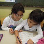 Es sind zwei Mädchen zu sehen, die gerade ein Schriftstück gemeinsam erarbeiten.
